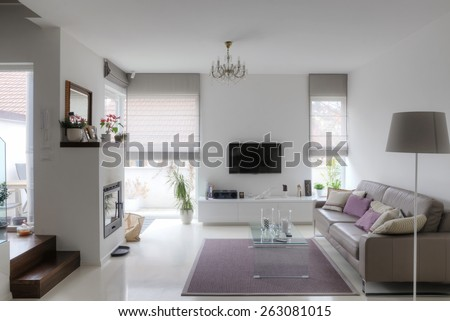 modern living room with taupe sofa glass table and fireplace - stock photo