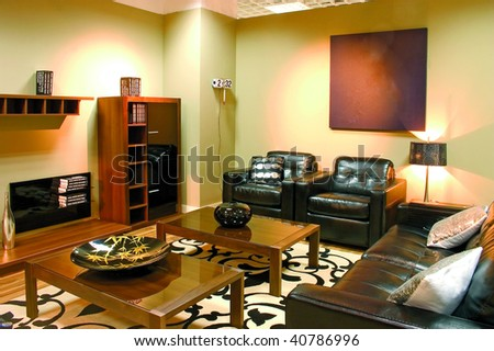 Modern living room with warm colors. Leather sofa, two arm-chairs and a coffee table. - stock photo