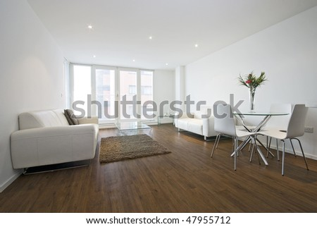 Modern living room with white leather sofas and a dining table for four - stock photo