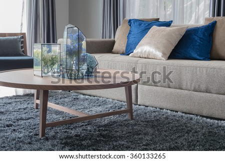 Modern Living Room With Wooden Round Table On Carpet