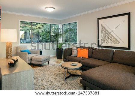 Modern living room within trees in mid century home with brown couch, hardwood floor, fire place, rug and round table. - stock photo