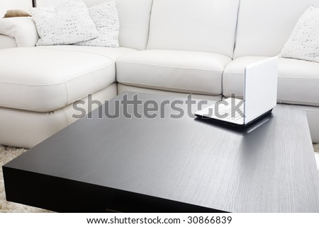 Modern livingroom. White furniture - sofa and couch with a laptop on table - stock photo