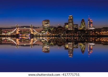 Modern London cityscape after sunset with reflection from Thames River - stock photo