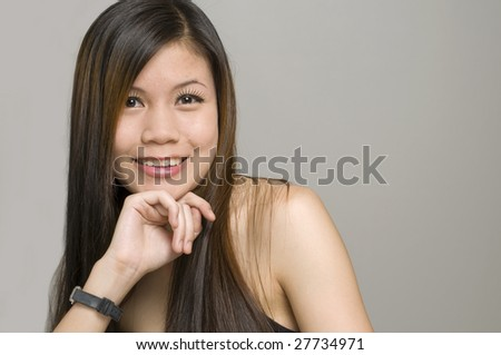 Modern looking Asian woman resting her head on her hand and looking at camera - stock photo