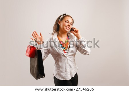Modern looking young woman wearing white jacket talking on the phone and holding shopping bags - stock photo