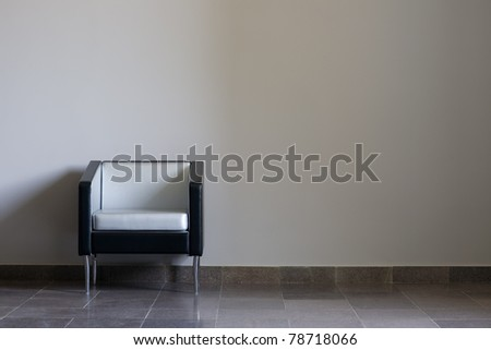 Modern lounge chair against a gray wall. Daylight. - stock photo