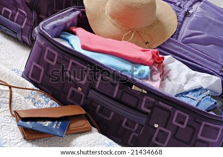 Modern luggage partially packed with colorful summer clothing.  US passport included in composition. - stock photo