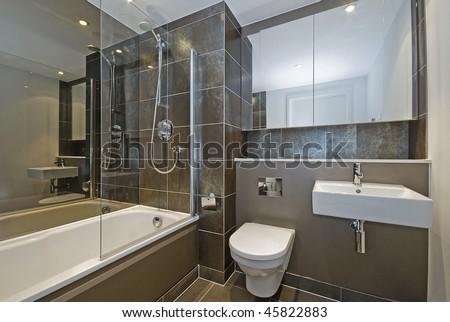 modern luxury bathroom with dark brown floor to ceiling tiles - stock photo