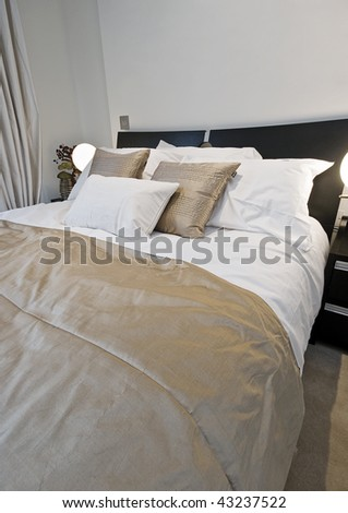 modern luxury bedroom detail with strown double bed - stock photo