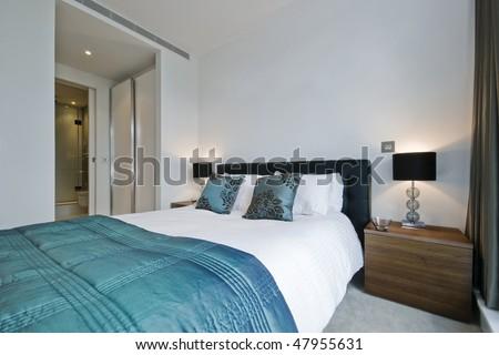 modern luxury bedroom with walk-in wardrobe and en-suite bathroom - stock photo