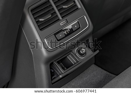 Modern luxury car central console with climate controls for rear passengers