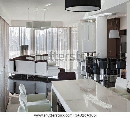 Modern luxury interior in minimalistic style: living room with big table and kitchen in daylight - stock photo