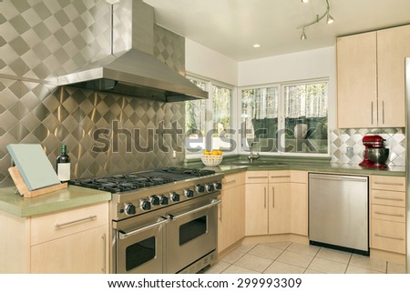 Modern luxury kitchen in light wood with all new stainless steel appliances. - stock photo