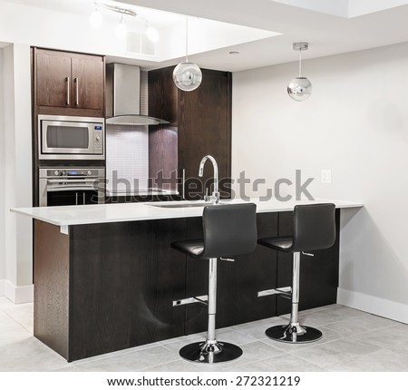Modern luxury kitchen interior with dark wood cabinets, island counter, bar stools and stainless steel appliances - stock photo
