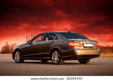 Modern luxury sedan with dramatic sunset sky - stock photo