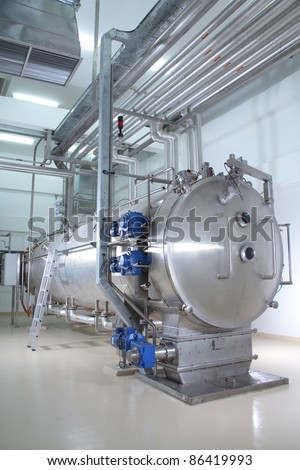 Modern machinery in a pharmaceutical production plant - stock photo