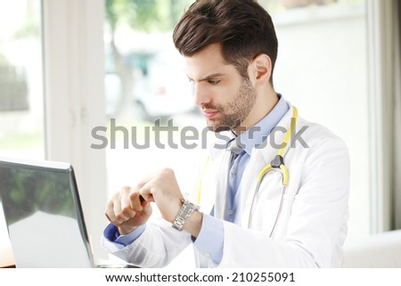 Modern male doctor working in private clinic.