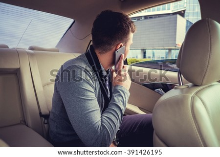 Modern man talking by smartphone in the car. - stock photo