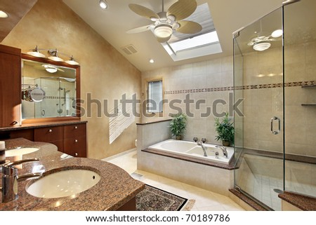 Modern master bath with glass shower and skylight - stock photo