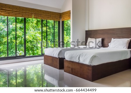modern master bedroom with twin beds and wide glass windows the design to give scenic