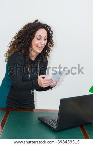 Modern mature woman, happy and smiling,  use the tablet. She has long curly hair and blacks, with green eyes. Cheerful and smiling. - stock photo
