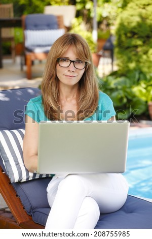 Modern mature woman working at home in garden. Small business.