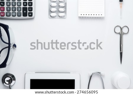 Modern medicine workplace with digital tablet, notepad, stethoscope, glasses, calculator, bottles, pills and syringes at doctor's desk. Copy space view from the top - stock photo