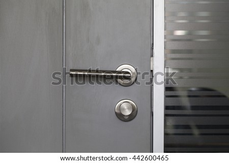 Modern metal door handle lock isolated with black wooden door and frosted glass wall in my meeting room