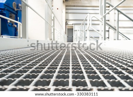 Modern metal steel grid floor inside a factory storage house. - stock photo