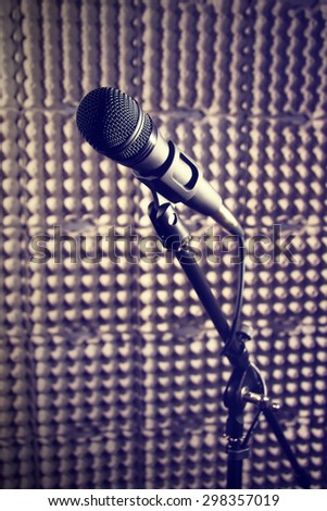 Modern microphone on a stand, recording studio, microphone  picture, sound wall, microphone stand, mesh wire, close-up shot, vertical image, images in dark colors. - stock photo