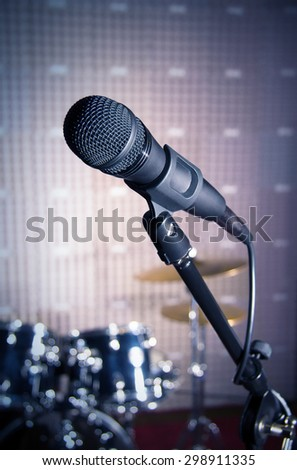 Modern microphone on a stand, recording studio, microphone picture, sound wall, microphone stand, drum set, mesh wire, close-up shot, vertical image, images in dark colors. - stock photo