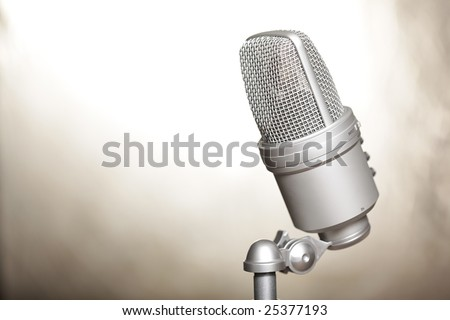 Modern microphone on creamy smooth metallic background