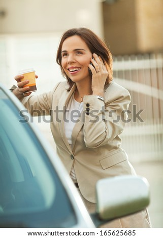 Modern mid adult businesswoman talking on the phone outdoors - stock photo