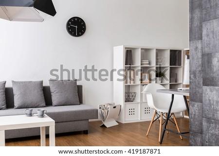 Modern,minimalist living room with resting space, racks and desk corner - stock photo