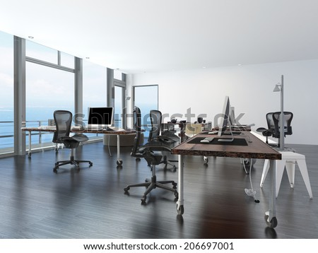 Modern minimalist office with computer work stations on wheeled tables in a spacious open plan room overlooking the sea - stock photo