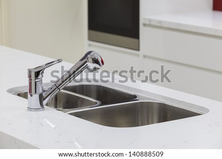 Modern mixer faucet in new kitchen - stock photo