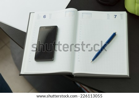 Modern Mobile Phone and Blue Pen on Clean Notebook on Black Table. - stock photo