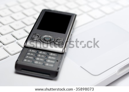 Modern mobile phone arranged with white laptop keyboard