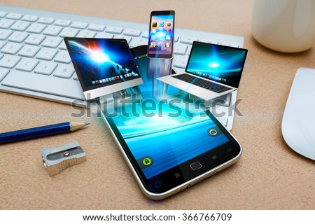 Modern mobile phone in office connecting tech devices together - stock photo