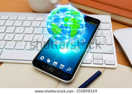 Modern mobile phone in office with cyber world flying over - stock photo