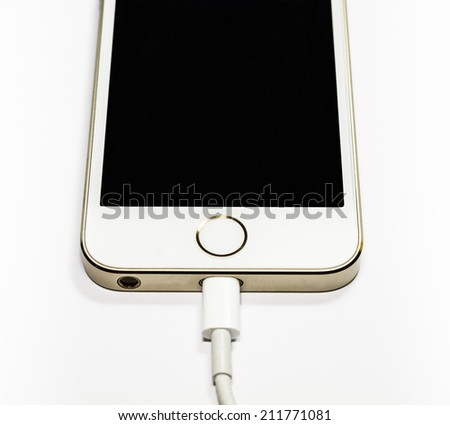 Modern mobile phone on charge. On a white background - stock photo