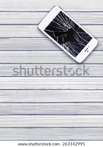 Modern mobile phone with broken screen on white wooden background - stock photo