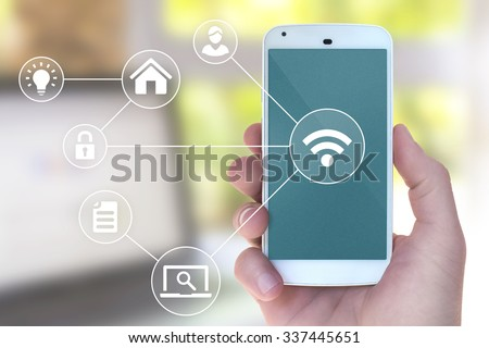 Modern mobile smart phone connecting to wifi automation apps in male hand with office laptop in bokeh style background - stock photo