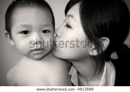 modern mother kissing son - in sepia tone - stock photo