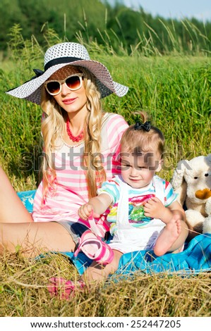Modern mother sunning with baby on nature - stock photo
