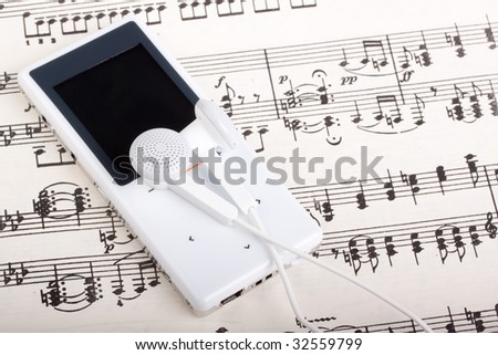 Modern MP3 player and note. Close up. - stock photo