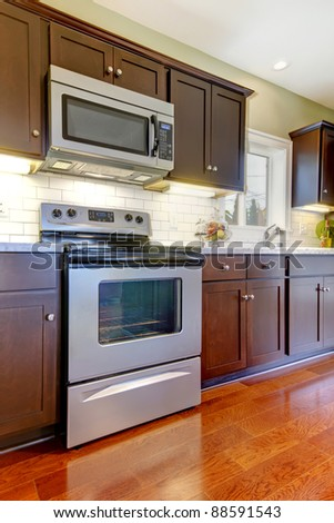 Modern new brown kitchen with cherry floor. - stock photo