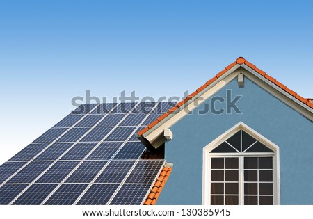 modern new built house, rooftop with solar cells, blue front with lattice window - stock photo