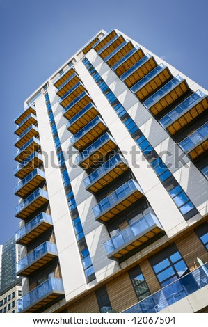 Modern, new executive apartment building with blue summer sky. - stock photo