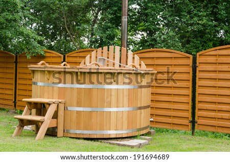 modern new wooden water spa hot tub with stairs outdoor  - stock photo